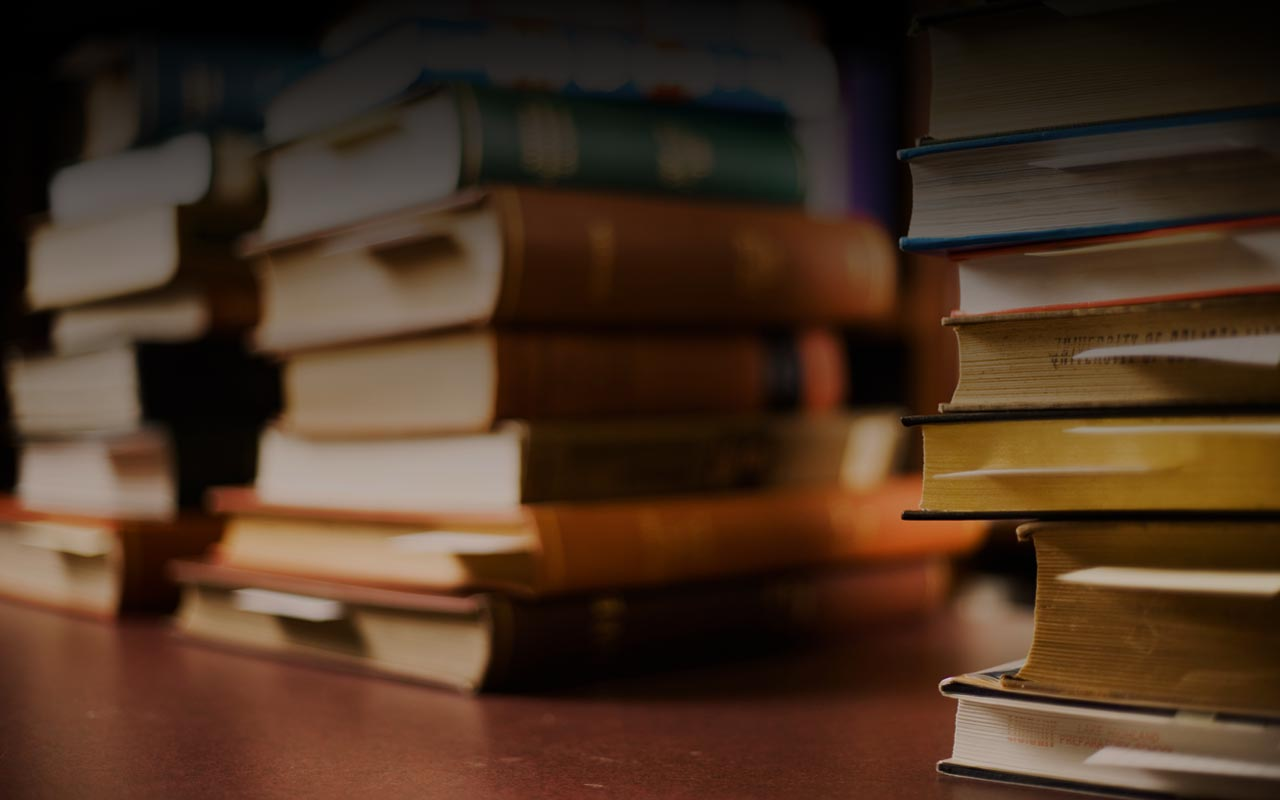 Background image of books piled up on a desk